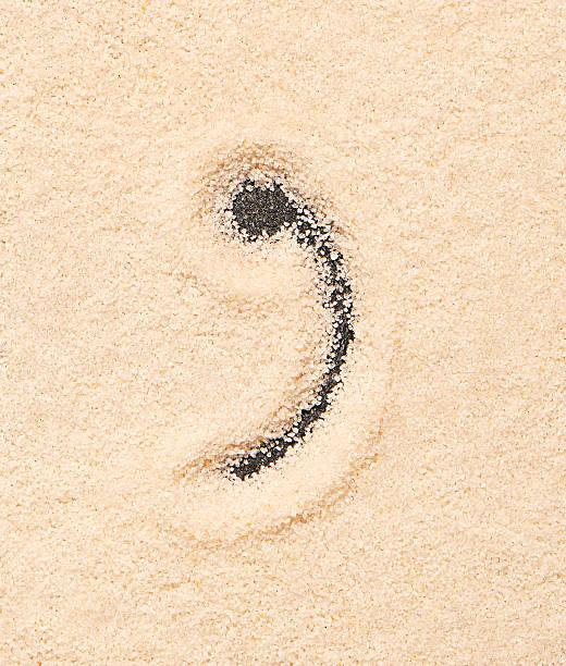 komma symbol geschrieben am sand - komma stock-fotos und bilder