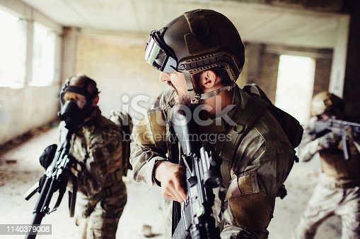 istock Commander is standing in a front and looking to his soldiers. They all are holding rifles. Men on the back wears uniform and masks. Front man is calling his partners to go forward. 1140379008