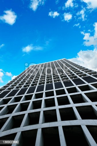 commanding modern skyscraper in close-up with bright sky, vertical frame (XL)