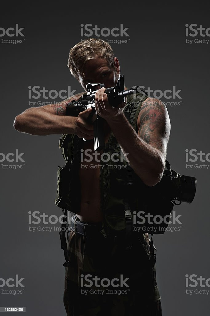 Commando aiming with an M16 assault rifle against dark background royalty-free stock photo