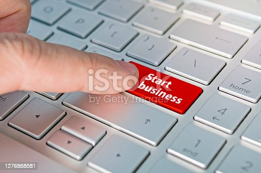 Commerce, Internet business, Start-up start business inscriptions on the grey silver keyboard button close up, Red button.
