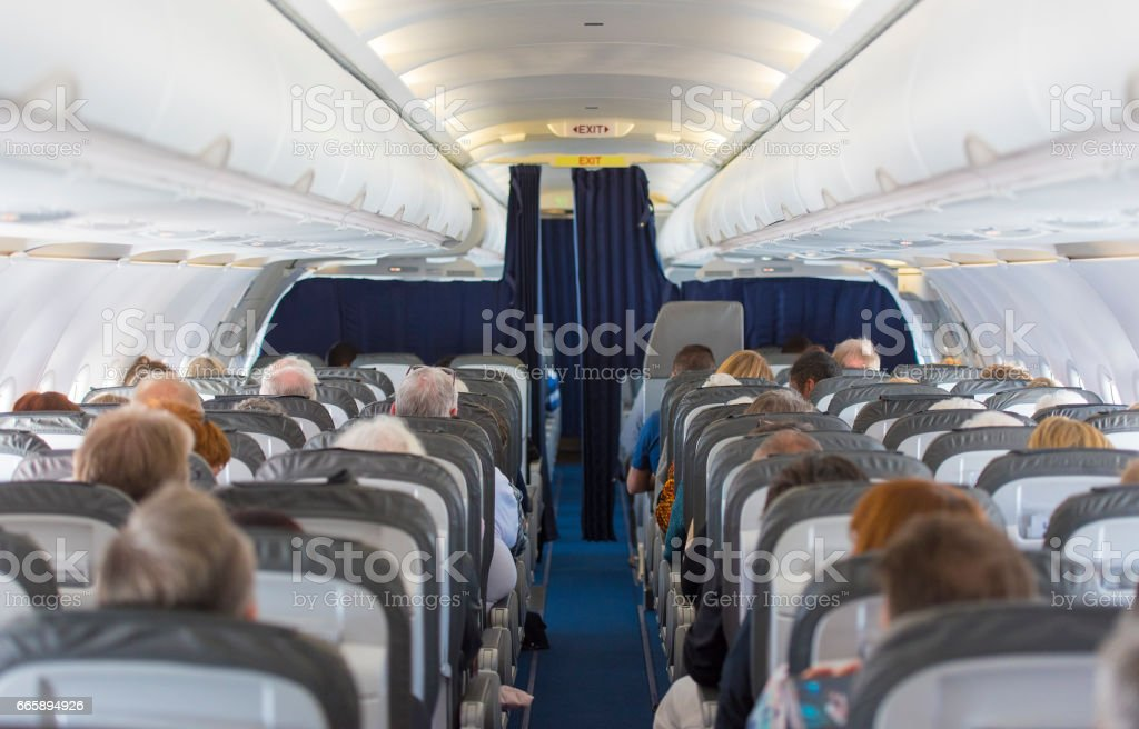Commercial aircraft cabin with passengers Commercial aircraft cabin with passengers Air Turbulence Stock Photo