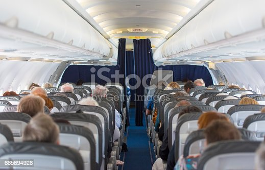 istock Commercial aircraft cabin with passengers 665894926
