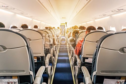 istock Commercial aircraft cabin with rows of seats down the aisle 1058285308