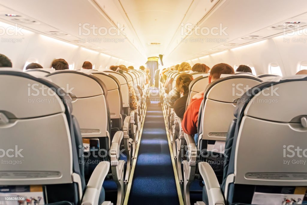 Commercial aircraft cabin with rows of seats down the aisle stock photo