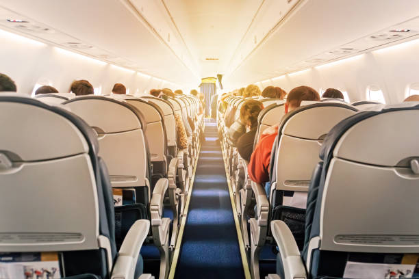 Commercial aircraft cabin with rows of seats down the aisle Commercial aircraft cabin with rows of seats down the aisle. morning light in the salon of the airliner. economy class passenger stock pictures, royalty-free photos & images