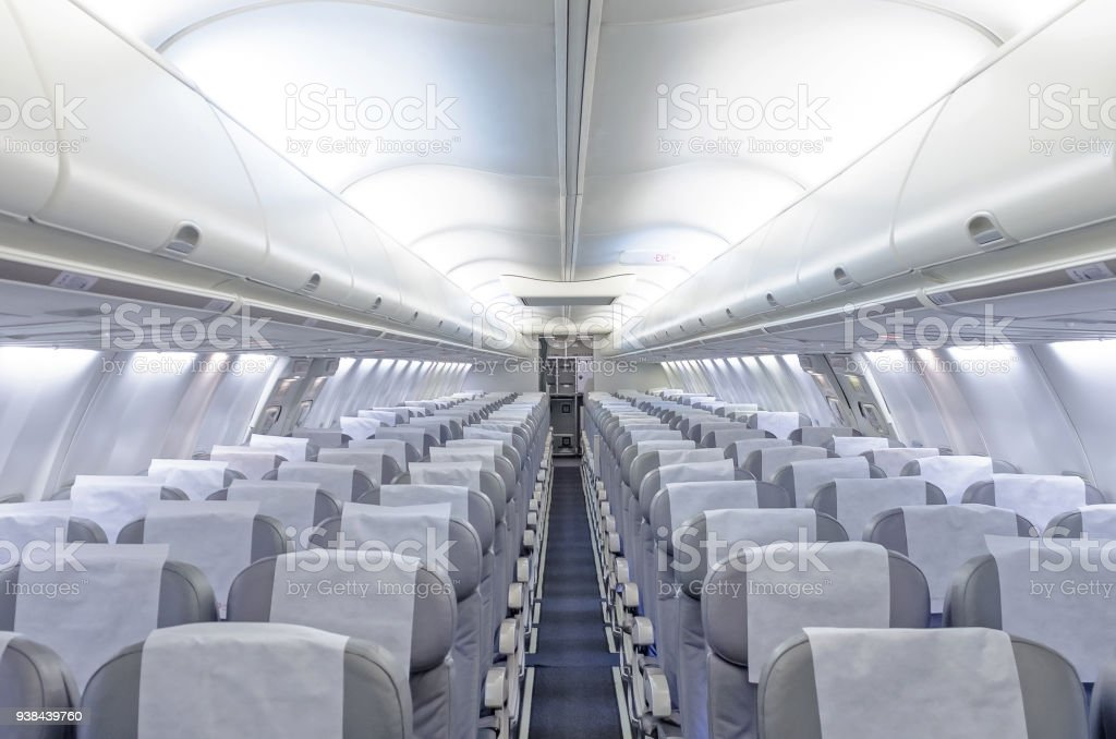 Commercial aircraft cabin with rows of seats down the aisle. stock photo