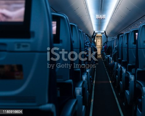Commercial aircraft cabin with rows of seats down the aisle stock