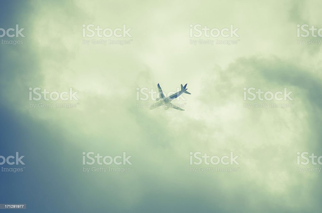 commercial airline disappearing behind clouds in monochrome royalty-free stock photo