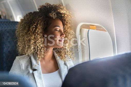 A young woman sits in the window seat of a commercial airliner and leans back with her eyes closed.