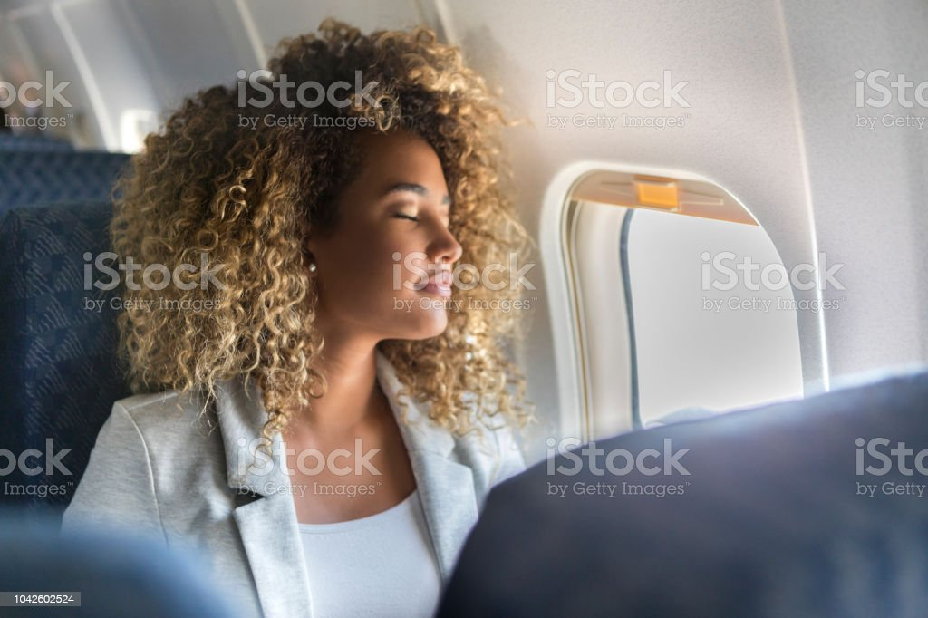 Commercial airline passenger sleeps in window seat stock photo
