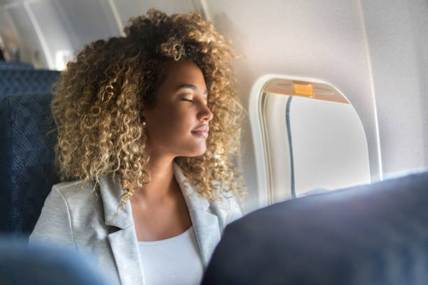 commercial airline passenger sleeps in window seat - aereo di linea foto e immagini stock