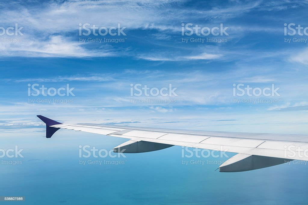 Commercial airline wing in high altitude flight stock photo