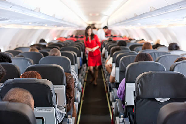 Commercial airliner cabin. Passengers inside the cabin of a commercial airliner during flight. Shallow depth of field with focus on the seats in the foreground. cabin crew stock pictures, royalty-free photos & images