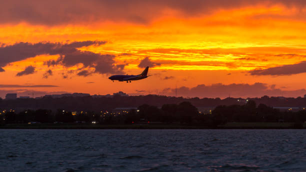 Commercial airliner landing at Reagan National Airport at sunset as storms and rain pass through A brilliant, bright orange sky appears at sunset over the Potomac River as a plane lands at Reagan National Airport ronald reagan washington national airport stock pictures, royalty-free photos & images