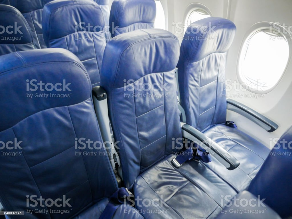 commercial airplane cabin with blue passenger seats. stock photo