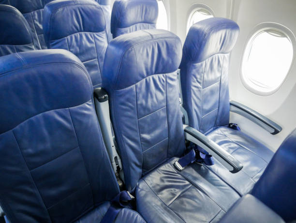 commercial airplane cabin with blue passenger seats. Interior of commercial airplane cabin with blue passenger seats. airplane seat stock pictures, royalty-free photos & images