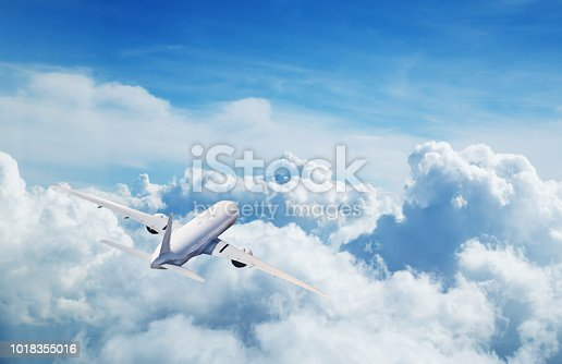 istock Commercial airplane flying above clouds 1018355016