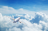 Back view of commercial airplane flying above clouds. Copyspace for text