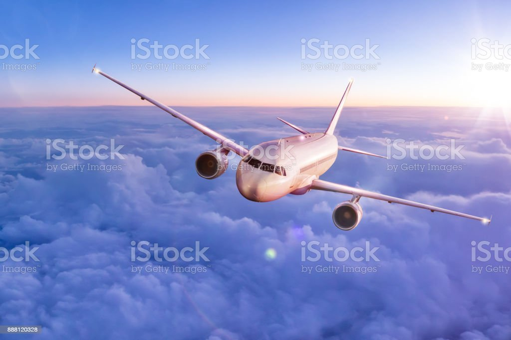 Commercial airplane flying above clouds stock photo