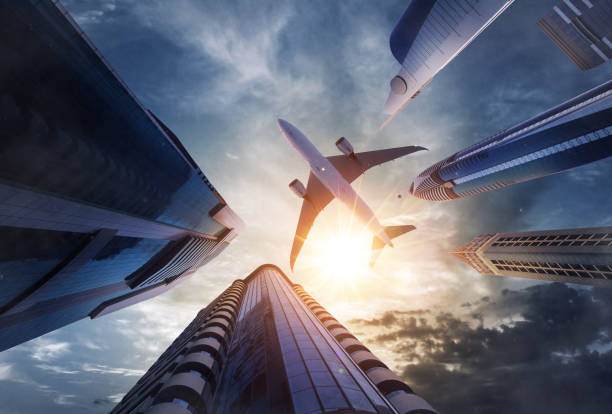 avion commercial volant au-dessus des gratte-ciels - au fond de photos et images de collection
