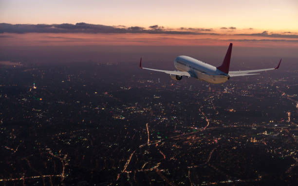 Commercial airplane flying over big city at dusk Commercial airplane flying over big city at dusk mid air stock pictures, royalty-free photos & images