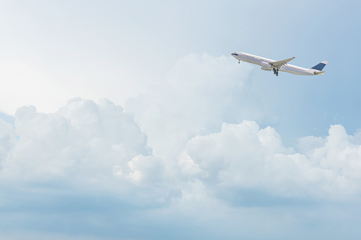 istock Commercial airplane flying over bright blue sky and white clouds. 673808780
