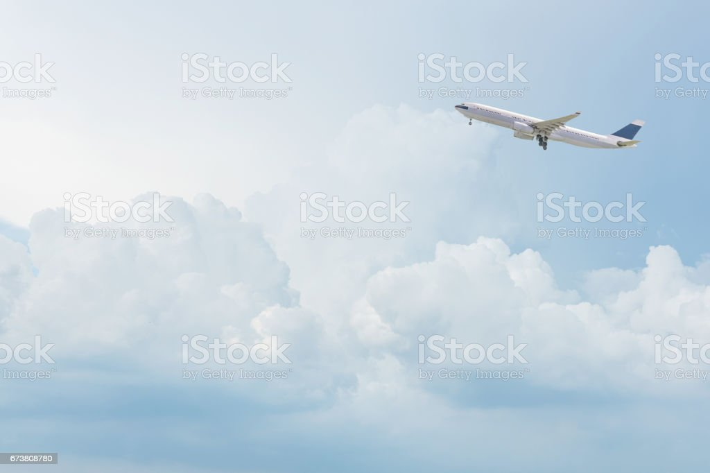 Avion commercial survolant de ciel bleu et nuages blancs. - Photo