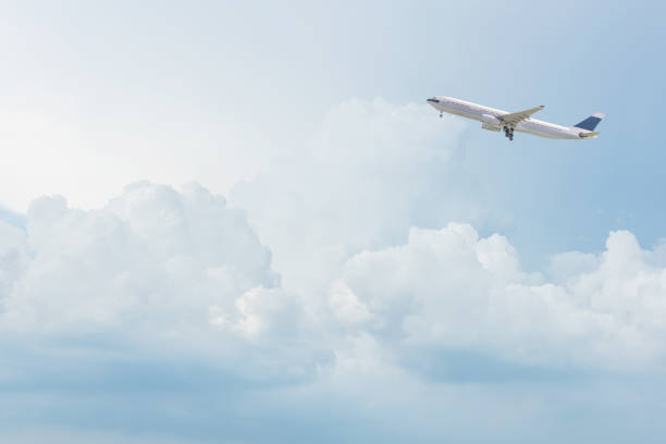 Commercial airplane flying over bright blue sky and white clouds. stock photo