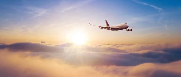Commercial airplane flying over dramatic sunset stock photo