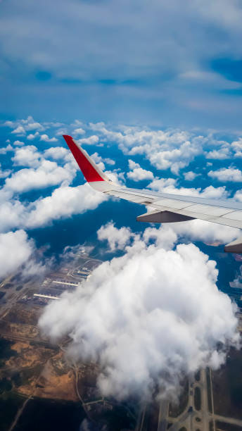 A commercial airplane flying over Kuala Lumpur skies A commercial airplane flying over Kuala Lumpur skies kuala lumpur airport stock pictures, royalty-free photos & images