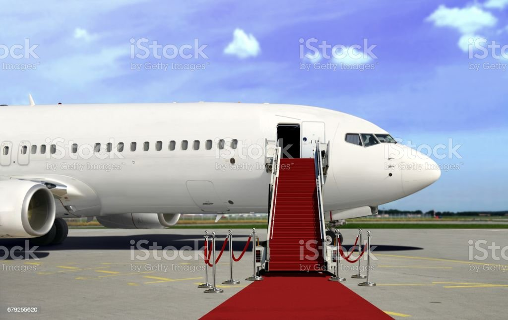 Commercial airplane in daylight with red carpet stock photo