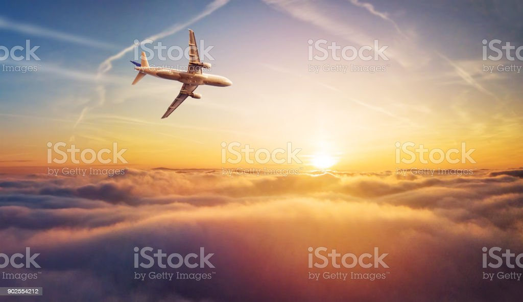 Commercial airplane jetliner flying above clouds in beautiful sunset light. stock photo