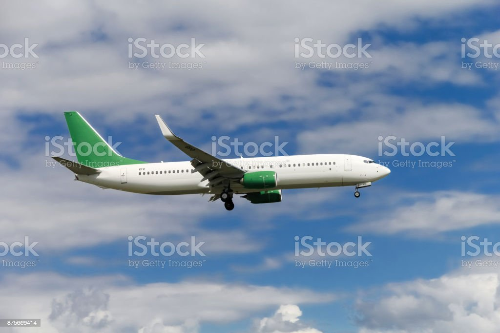 Commercial airplane landing at the airport with cloudy sky in the background stock photo