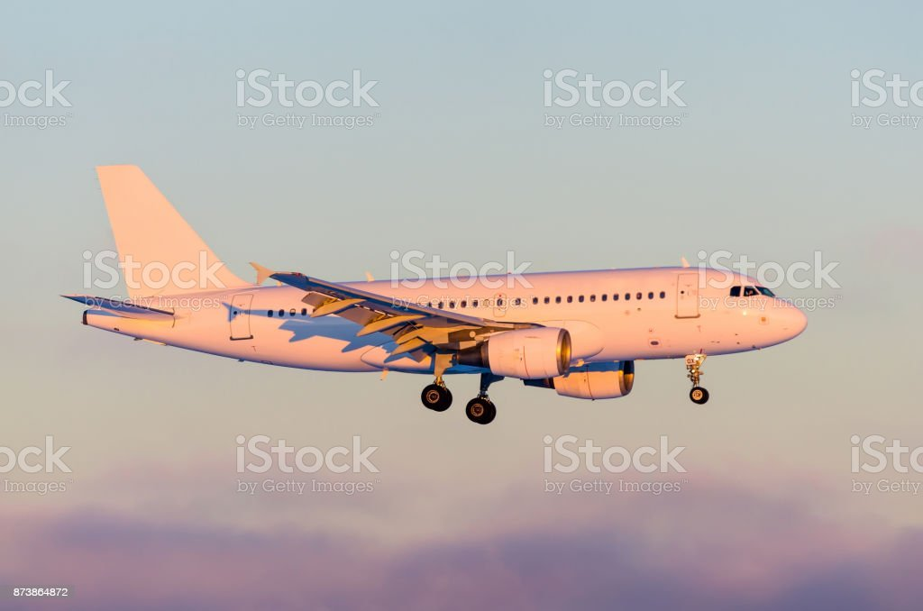 Commercial airplane landing in dramatic sunset light. stock photo