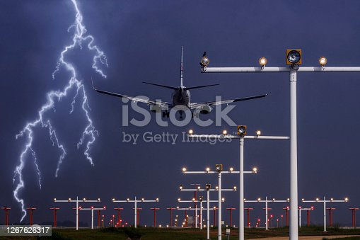Passenger aircraft approaching airport runway in violent storm, lightning and thunder. Concept of emergency situation