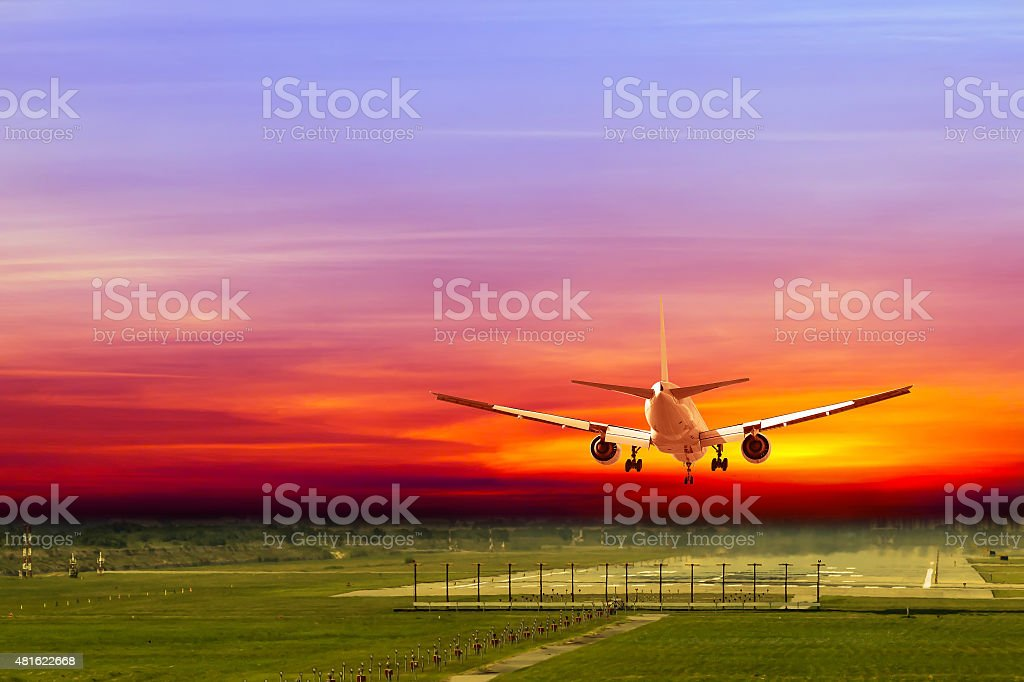 Commercial airplane landing on runway in airport at sunset stock photo