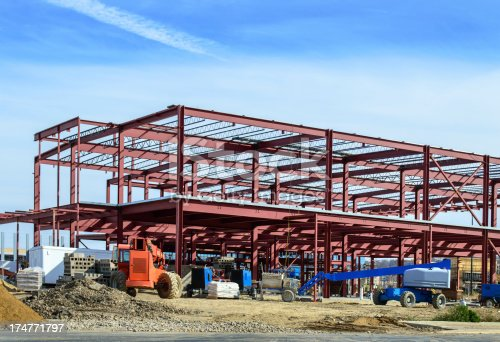 Commercial construction site showing Steel I beams and steel framing for a new commercial building with equipment in the foreground and sky in the background.