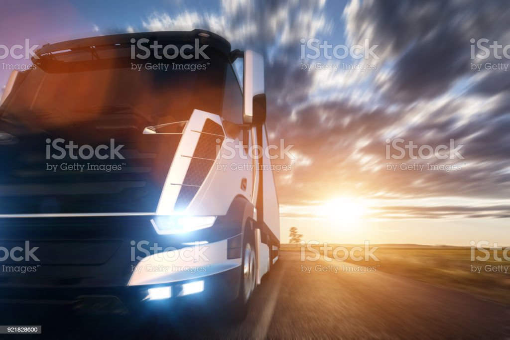 Commercial cargo delivery truck with trailer driving on highway at sunset. stock photo
