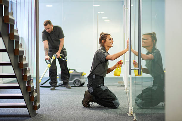 commercial cleaning contractors a female cleaning contractor is polishing the glass partition offices whilst In the background a male colleague steam cleans an office carpet in a empty office in between tenants.  .The female is smiling . cleaning equipment stock pictures, royalty-free photos & images