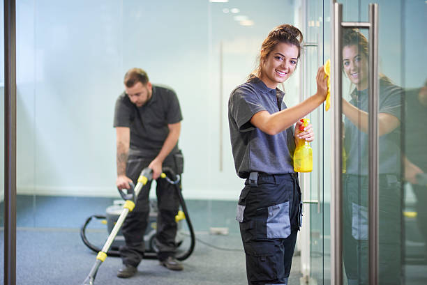 commercial cleaning contractors a female cleaning contractor is polishing the glass partition offices whilst In the background a male colleague steam cleans an office carpet in a empty office in between tenants.  .The female is smiling to camera. cleaner stock pictures, royalty-free photos & images