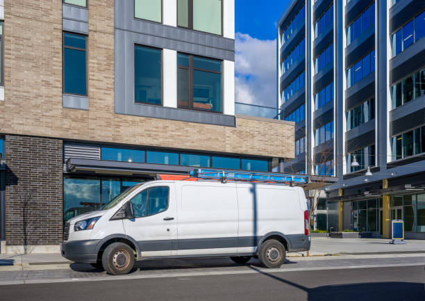 Commercial compact mini van for small business and deliveries standing on urban city street with multilevel apartments buildings stock photo