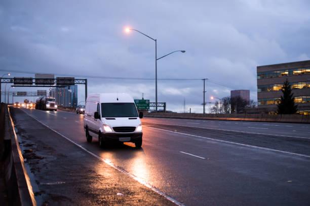Commerciale Monospace compact pour la livraison de colis et de marchandises sur route rugueuse avec la réflexion de la lumière sous une pluie de la chaussée de pluie. - Photo