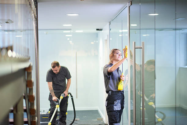 commercial deep clean a female cleaning contractor is polishing the glass partition offices whilst In the background a male colleague steam cleans an office carpet in a empty office in between tenants.  . cleaner stock pictures, royalty-free photos & images
