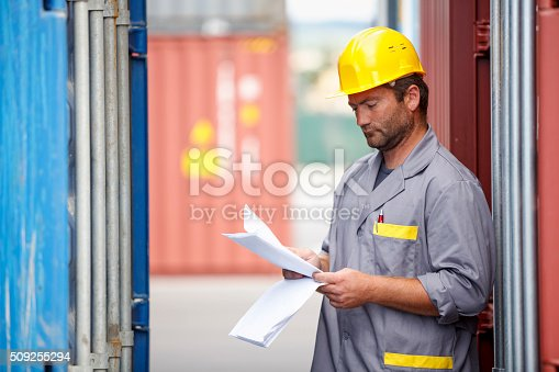 184640907istockphoto Commercial docks worker examining containers 509255294