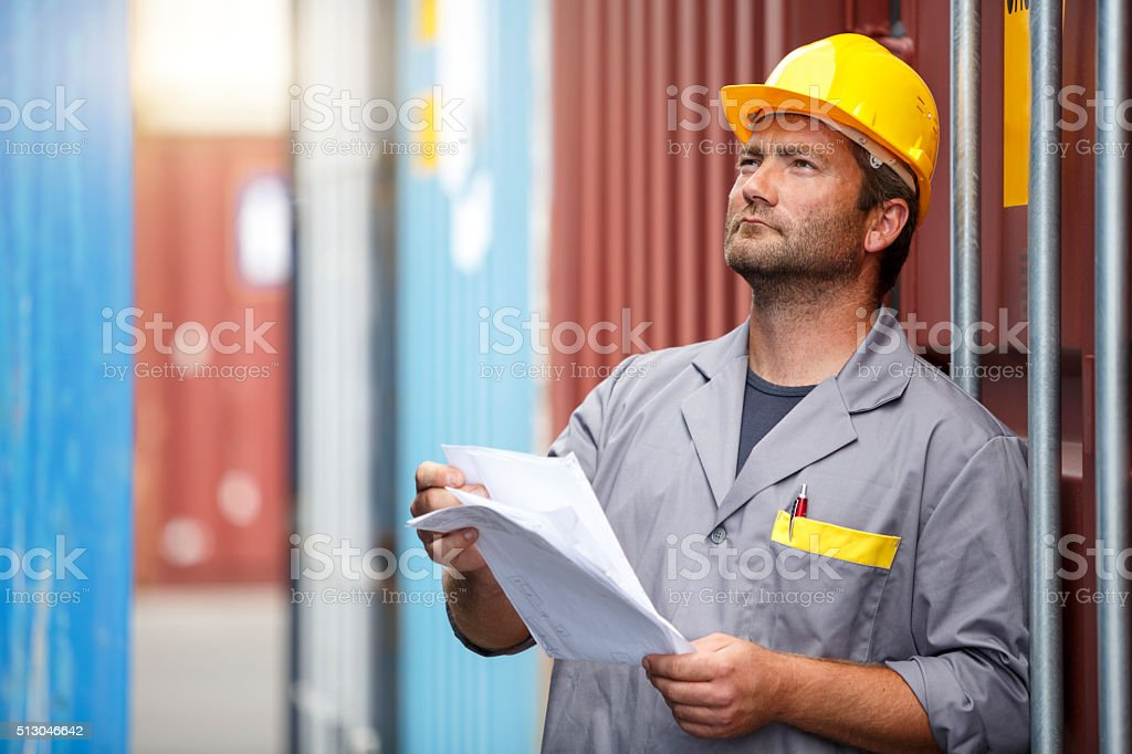Commercial docks worker examining containers stock photo