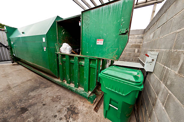 Commercial Dumpster With Compactor A large combination compactor/dumpster that serves a large apartment community. compactor stock pictures, royalty-free photos & images