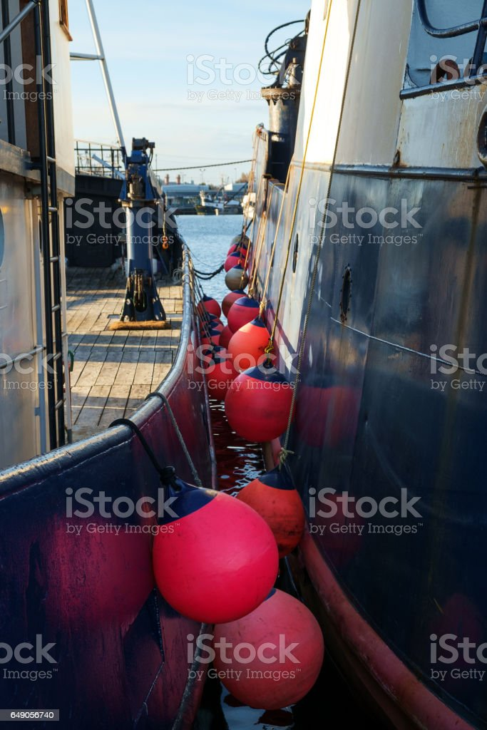 Commercial fishing boats tied together stock photo