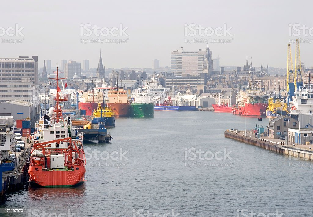A commercial harbor with multiple multi color ships stock photo