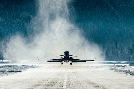 Commercial jet departing with snow blasting away
